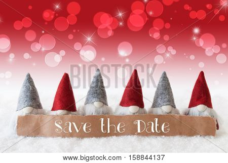 Label With English Text Save The Date. Christmas Greeting Card With Gnomes. Sparkling Bokeh And Red Background With Snow And Stars.