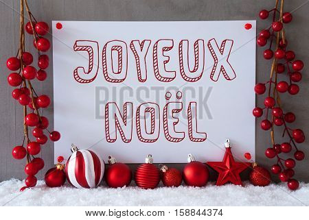 Label With French Text Joyeux Noel Means Merry Christmas. Red Christmas Decoration Like Balls On Snow. Urban And Modern Cement Wall As Background.