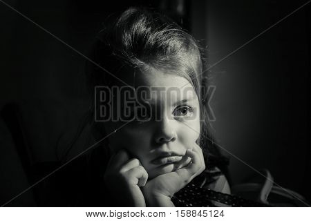 nice amazing closeup view of monochrome portrait of a lonely sad little girl sitting alone in dark room