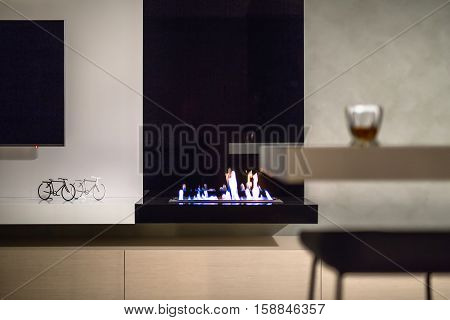 Fire in the black fireplace in the interior in a modern style with light walls. There is a TV, white rack with black and white decorative bicycles, wooden lockers, glass on the tabletop, stool.