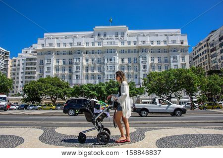 16 November 2016. Rio de Janeiro, Brazil. Young beautiful woman wearing white dress and flip-flops, walking along Avenida Atlantica with black baby carriage with toys on the background of Copacabana Palace