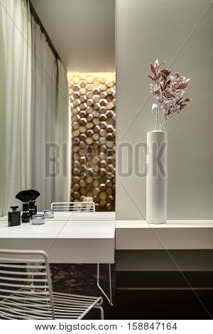 White tabletop with a mirror in the room in a modern style. There is a perfume, cream and a brush on it and a white chair under it. Next to the tabletop there is a white rack with a flower in a vase.