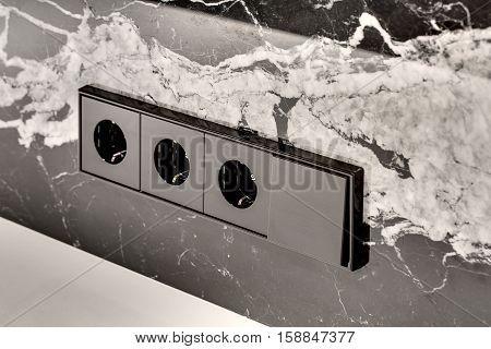 Black power sockets with the switch on the black marble wall with the white patterns. Closeup. Horizontal.