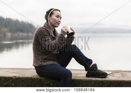 Woman with coffee by the lake in north Idaho.