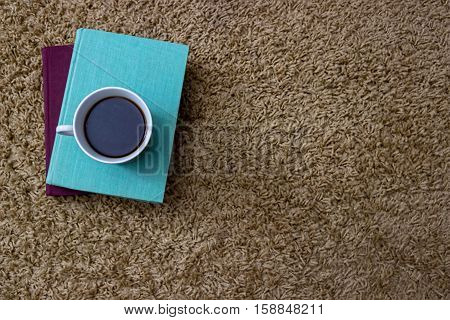 Green and blue books with a porcelain cup of coffee on a beige carpet.Light brown background.