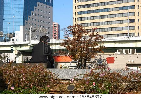 A business man is sitting in the city public park. Asian man wear headphone and listening music in the city.