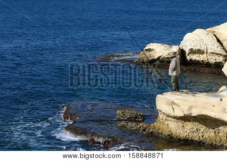 fisherman with a fishing rod on the shore of the Mediterranean Sea in the north of Israel