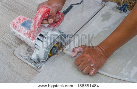 Man using electric tile cutter using water ripped the tiles to get the tiles for flooring and ceramic