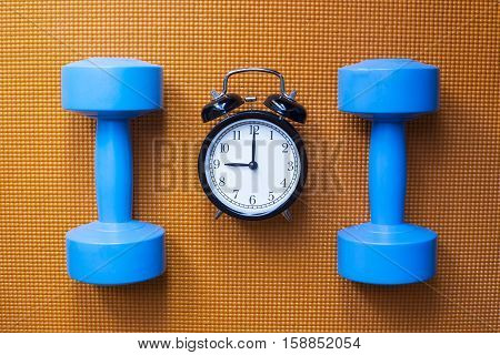 Time for exercising clock and dumbbell with yoga mat background