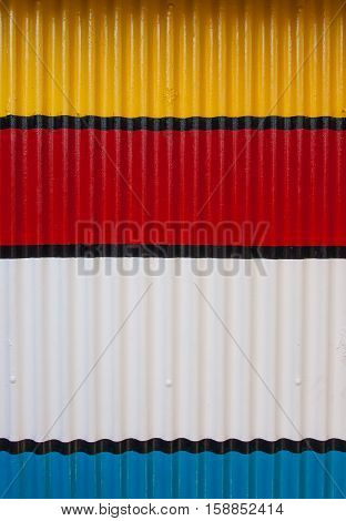 Corrugated paint metal in yellow, red and white
