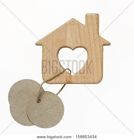 wooden toy house with chimney and heart shape window isolated on the white background. three blank circle paper tags attached on a rope.