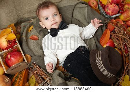 autumn little boy lie on yellow fall leaves, apples, pumpkin and decoration on textile