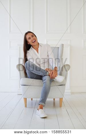 Portrait of young brunette smiling at camera while sitting in a cosy armchair in white room white brick background in a modern casual clothes