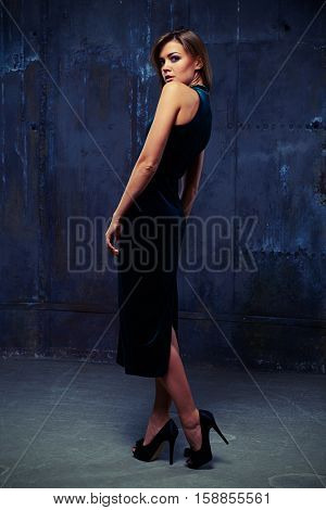 Mid side full-length shot of sensual brunette in sling velvet dress looking over her shoulder while posing at the camera in studio in dim light