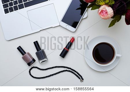 A mid shot of a selection of different things on the table including three nail polishes, red lipstick and necklace, small box and mobile on laptop