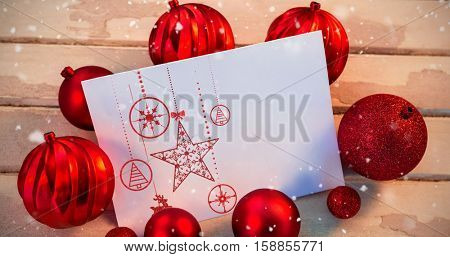 Snow falling against christmas bauble ball and paper on wooden plank