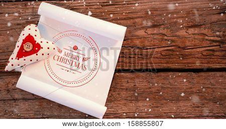 Snow falling against heart and blank paper on wooden plank