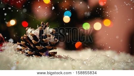 Snow falling against christmas bauble and pine cone on snow