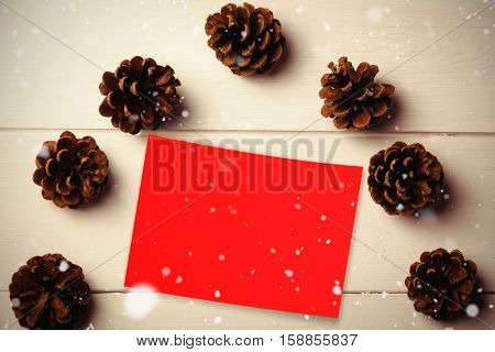 Snow falling against pine cone on wooden table