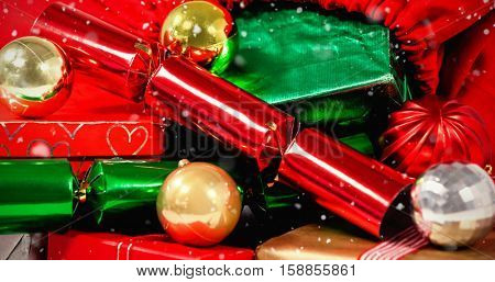 Snow falling against close-up of christmas presents and bauble