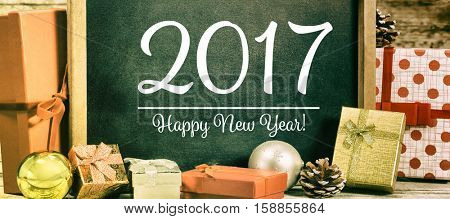 Slate with happy new year text and gift against wooden wall