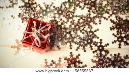 Snow falling against small wrapped gift box and snowflake scattered on wooden table