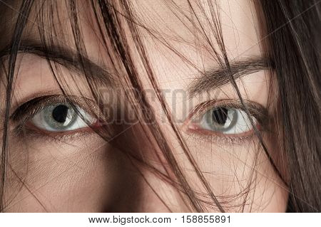 scared female eyes under blowing hair close up macro image