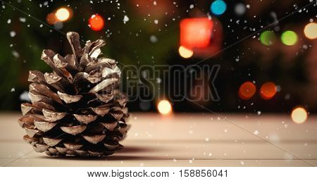 Snow falling against close-up of pine cone on wooden table