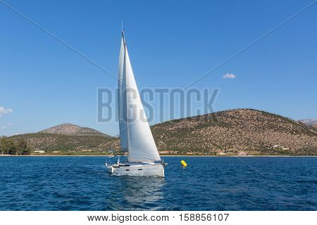 Sailing yachts boat with white sails in regatta at the sea.