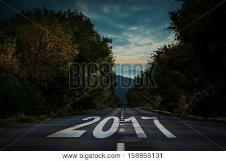 Happy New Year 2017 against open road background