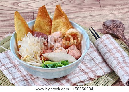 Thai noodle with pink tofu soup topped rugby fishball ,wonton ,porkball ,boiled porkblood ,pork rind ,coriander and white mushroom call Yen Ta Fo in Thai.