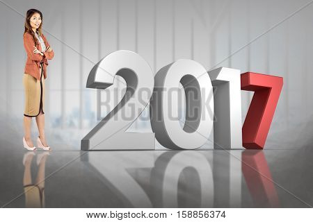 Smiling businesswoman with crossed arms against modern building against cityscape with 3D new year