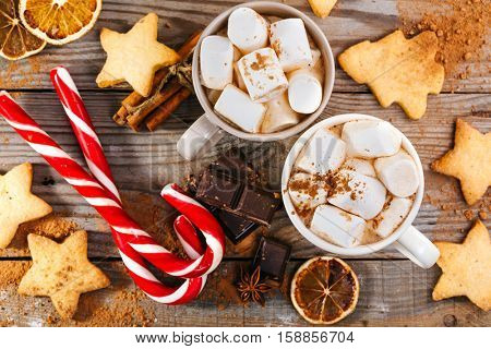 Christmas hot drink. Cocoa with marshmallows, chocolate and cinnamon on wooden background