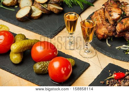 Fried meat, potatoes, vegetables on black slate plates and two shot glasses with cognac in style a rustic