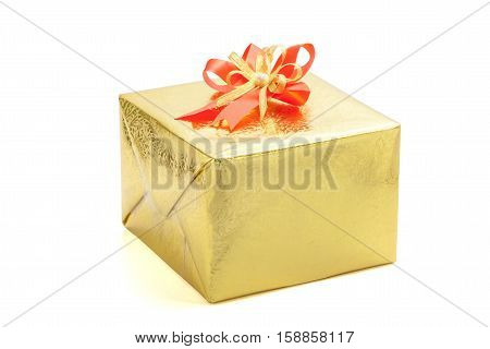 A gold gift box with red ribbon bow on white background New Year & Merry Christmas greeting.