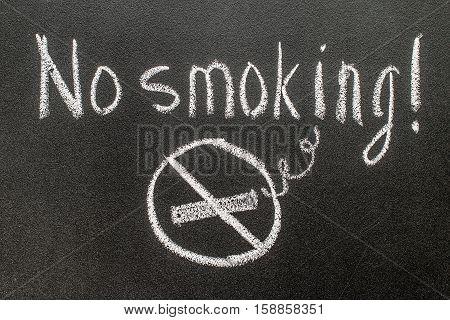 No smoking   hand writing chalk text on black chalkboard