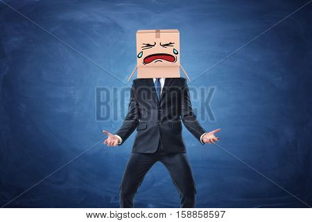 Businessman wearing cardboard box with drawn crying face on his head. on blue chalkboard background. Anonymous person. Issues of small business. Bear losses.