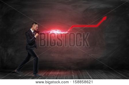 A businessman putting out his hand like a fighter and making a red kinked arrow standing on a wooden floor and an empty blackboard behind him. Business strategy. Pursuit of success. Practical energy.