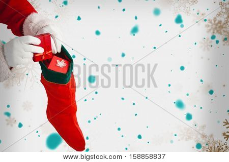 Santa Claus putting presents in Christmas stockings against snowflake pattern