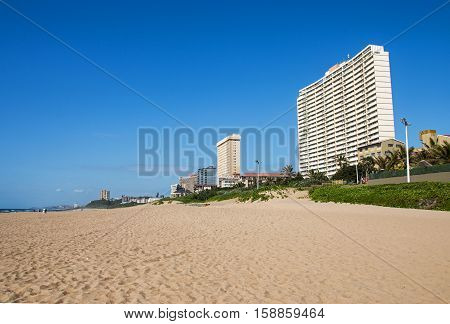 Vegetation And Empty Beach Against City Skyline