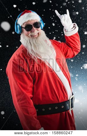 Santa claus showing hand yo sign while listening to music on headphones against snowflake pattern