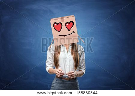 Young beautiful businesswoman with cardboard box on her head with drawn smiley face with hearts instead of eyes. Anonymous person. Falling in love. Office romance. Love customers.