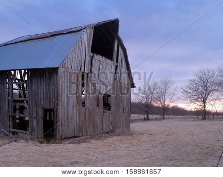 old barn surrounded by trees and sunset
