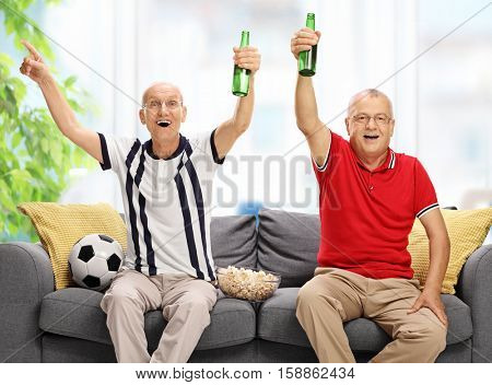 Overjoyed seniors seated on a sofa watching football and cheering