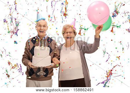 Overjoyed seniors celebrating a birthday with a cake and balloons isolated on white background