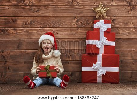 Merry Christmas and Happy Holidays concept. Cute little girl with christmas presents on wooden background. Portrait of beautiful child in Santa hat with gifts.