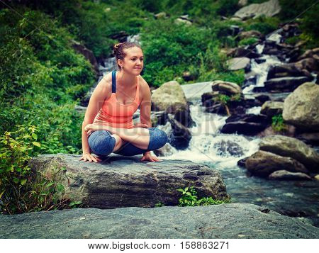 Vintage retro effect filtered hipster style image of Yoga exercise outdoors -  woman doing Ashtanga Vinyasa Yoga arm balance strength training asana Tolasana - scales pose at waterfall in Himalayas