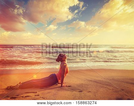 Vintage retro hipster style image of Yoga outdoors on beach - woman practices Ashtanga Vinyasa yoga Surya Namaskar Sun Salutation asana Urdhva Mukha Svanasana - upward facing dog pose on sunset