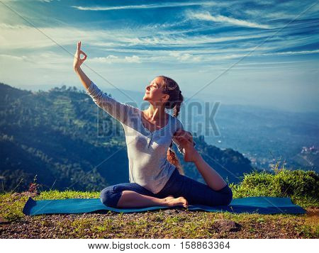 Yoga outdoors - sporty fit woman doing stretching yoga asana Eka pada rajakapotasana - one-legged king pigeon pose in Himalayas mountains, India. Vintage retro effect filtered hipster style image.