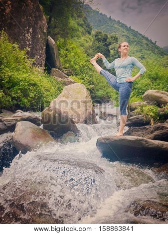 Yoga outdoors - woman doing Ashtanga Vinyasa Yoga balance asana Utthita Hasta Padangushthasana - Extended Hand-To-Big-Toe Pose posture at waterfall. Vintage retro filtered hipster style image.